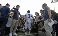 Kwansei Gakuin University American football team quarterback Kosei Okuno, center, fields questions from reporters follwing a game in Suita, Osaka Prefecture, on May 27, 2018. (Mainichi)