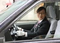 「日の丸交通」のタクシードライバーとして働くトランスジェンダーの長本奈緒さん。女性の制服を支給され、ほほ笑む=東京都中央区で、後藤由耶撮影
