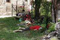 昼下がりの暑い時間、巡礼道沿いの日陰で昼寝をしてやりすごす巡礼者たち