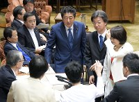 Prime Minister Shinzo Abe, center, looks at directors of the House of Councillors Budget Committee, who surround the panel's chairman after the prime minister's remark caused deliberations to halt, on May 28, 2018. (Mainichi)