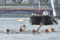 Swimmers demonstrate the traditional Japanese style of swimming in hopes of being allowed to join the torch relay for the 2020 Tokyo Olympic and Paralympic Games, in the Sumida River, on the border between Tokyo's Sumida and Taito wards, on May 27, 2018. (Mainichi)