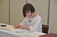 Takako Morita writes the names of newly confirmed atomic bomb victims into the registry at the Nagasaki Municipal Government on May 28, 2018. (Mainichi)