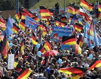 AfD supporters wave flags in Berlin, Germany, Sunday, May 27, 2018. The AfD that swept into Parliament last year on a wave of anti-migrant sentiment is staging a march, on through the heart of Berlin to protest against the government. (AP Photo/Markus Schreiber)