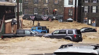 Water rushes through Main Street in Ellicott City, Md., on May 27, 2018. (Libby Solomon/The Baltimore Sun via AP)