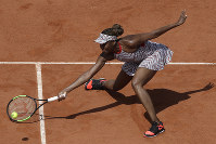 Venus Williams of the U.S. returns the ball to China's Qiang Wang during their first round match of the French Open tennis tournament at the Roland Garros Stadium, on  May 27, 2018 in Paris. (AP Photo/Alessandra Tarantino)