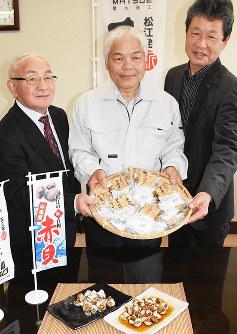 完成した赤貝の新商品を手に笑顔を見せる中海漁業協同組合の外谷久人組合長(中央)ら=松江市役所で、前田葵撮影