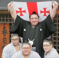 Tochinoshin, center, poses for a commemorative photo while holding a Georgian national flag after being promoted to sumo's second-highest rank of ozeki in front of Kasugano sumo stable in Tokyo's Sumida Ward on May 30, 2018. (Mainichi)