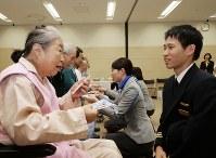 入院患者に、すずらんのしおりを手渡した古川雄大副操縦士(右)=東京都渋谷区の日本赤十字社医療センターで2018年5月31日午前10時57分、米田堅持撮影