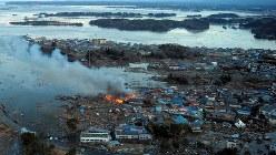 東日本大震災で、海岸線一帯が津波で水没し、火災が発生した住宅=福島県相馬市で2011年3月11日午後5時25分、本社機から貝塚太一撮影