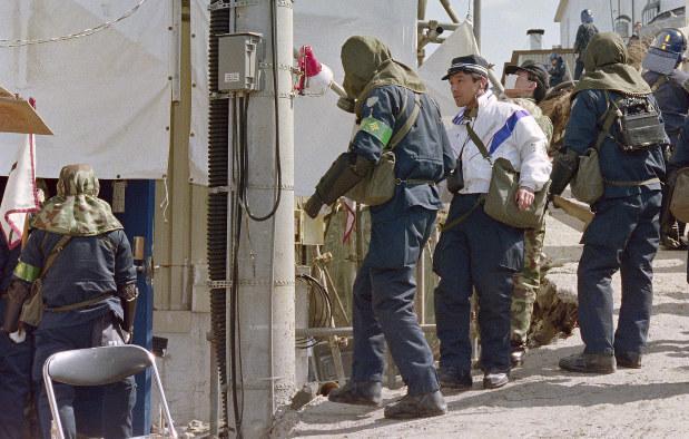 オウム真理教の教団施設家宅捜索で、自衛隊から貸与された防毒マスクを着用して施設内に入る警視庁の機動隊員たち=山梨県上九一色村(現富士河口湖町)で1995年3月22日