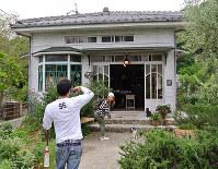 ロケセットだった「雑貨ハーブカフェ コリコ」の前で、ほうきにまたがって記念撮影を楽しむ観光客ら=香川県小豆島町で、倉田陶子撮影