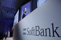 In this July 20, 2017, file photo, SoftBank Group Corp. Chief Executive Officer Masayoshi Son, left, speaks during a SoftBank World presentation at a hotel in Tokyo. (AP Photo/Shizuo Kambayashi)