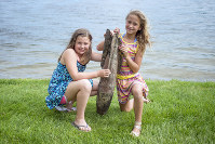 In this May 30, 2018 photo, Paige Burnett, 10, left, and Sage Menzies, 9 pose with a World War I practice bomb they discovered the day before while swimming in Lobdell Lake behind the Menzies' home in Linden, Mich. (Jake May/The Flint Journal via AP)