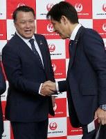 Japan national soccer team head coach Akira Nishino, right, shakes hands with Japan Football Association President Kozo Tashima during a departure ceremony at Narita International Airport on June 2, 2018. (Mainichi)