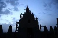 モスクの尖塔に泥を塗り始める男たち=マリ・ジェンネで2018年4月15日、写真家の長倉洋海さん撮影