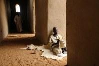 グランドモスク内は建物を支えるための柱が多い。その柱に寄りかかりイスラムの勉強をするセネガル人の留学生。最初は写真を拒まれたが、「世界でイスラムが誤解されているから」と説得すると撮らせてくれた=マリ・ジェンネで2018年4月9日、写真家の長倉洋海さん撮影