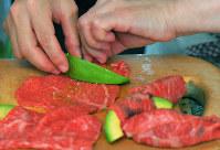 アボカドは縦半分に切り、種を除いて皮をむき、8~10枚のくし形に切りにし、肉にアボカドを一つずつのせ、端から巻く=手塚耕一郎撮影