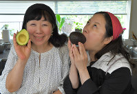 アボカドを持って笑顔の枝元なほみさん(左)と西原理恵子さん=手塚耕一郎撮影