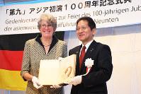 記念式典で徳島県鳴門市の泉理彦市長(右)に100年前の演奏会プログラムを手渡すペトラ・ボーナーさん=同市内で、大坂和也撮影