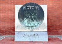 1997年の夏の甲子園で優勝したメンバーがマウンドに集まる様子が彫られている記念碑。この中に中谷仁コーチもいた=和歌山市冬野の智弁和歌山高校で、木原真希撮影