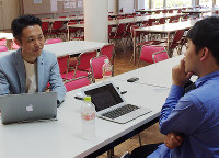 釈大智さん(右)と打ち合わせをする霍野廣由さん=大阪市内で、玉木達也撮影