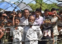 A man, center, explains his distrust of the Myanmar government in the border area between Myanmar and Bangladesh on May 28, 2018. (Mainichi)