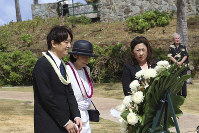 Japan's Prince Akishino, left, and Princess Kiko, center, stand before a wreath at the Ehime Maru Memorial in Honolulu on June 4, 2018. (AP Photo/Audrey McAvoy)