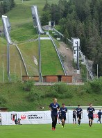 Players of Japan's national soccer team jog on a field with ski jumps in the background, in Seefeld, Austria, on June 3, 2018. (Mainichi)