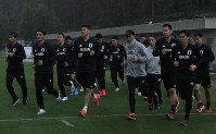 Players of Japan's national soccer team jog in the rain after arriving at a training camp in Seefeld, Austria, on June 2, 2018. (Mainichi)