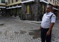 自爆テロがあったサンタ・マリア教会前で、犠牲になった兄弟が倒れていた当時の状況を説明する警備員のアリさん=インドネシア・ジャワ島東部スラバヤで2018年6月5日、武内彩撮影