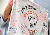 全国優生保護法被害弁護団が主催した集会で激励の寄せ書きを手にする被害者の姉=参院議員会館で2018年6月6日午後5時20分、梅村直承撮影