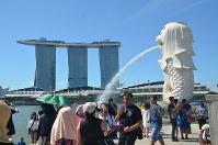 マーライオンと、シンガポールを代表する建物の一つであるホテル「マリーナベイ・サンズ」(左奥)の前で記念写真を撮る観光客ら=2018年6月4日、シンガポールで工藤哲撮影