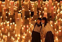 Visitors take photos in front of candles arranged for