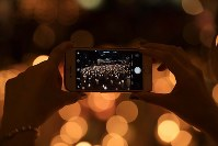A visitor uses a smartphone to take photos of candles arranged for