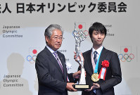 Figure skating star Yuzuru Hanyu, right, receives a special distinction award trophy from Japanese Olympic Committee President Tsunekazu Takeda at the JOC Sports Award ceremony in Chiyoda Ward, Tokyo, on June 8, 2018. (Mainichi)