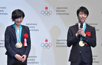 Figure skating star Yuzuru Hanyu, right, who won a special distinction prize at the JOC Sports Awards, is interviewed during the award ceremony in Chiyoda Ward, Tokyo, on June 8, 2018. Miho Takagi, left, a gold medalist in the women's team pursuit, also attended the ceremony. (Mainichi)