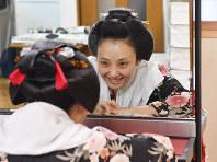 襟替え直前にだけ結う、舞妓の最後の髪型である「先笄(さっこう)」。「早く先笄に結ってもらいたい」と楽しみにしていた。鏡をのぞき込んでうれしそうな表情を見せる茉利佳さん。その後、静かに目を閉じると涙がにじんだ=京都市東山区で2018年5月14日、川平愛撮影