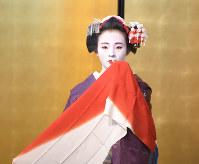 舞妓特有の赤い舞手ぬぐいを手に、大勢の観客の前で京舞を披露した。舞妓3年目ごろから結う「おふく」と呼ばれる髪型。桜の花かんざしとともに、祇園甲部の「都をどり」の提灯を髪に飾った。襟替えをして芸妓になると、舞手ぬぐいの色は紫に変わる=京都市東山区で2018年4月27日、川平愛撮影