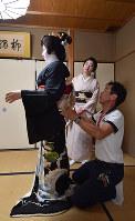 襟換え当日、男衆さんが着付けをし、最後に帯を締めた。同じ屋形の先輩芸妓である紗月さん(奥)も見守った=京都市東山区で2018年5月25日、川平愛撮影