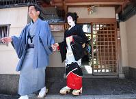 男衆さん(左)の付き添いで、屋形を出てあいさつ回りに向かう茉利佳さん=京都市東山区で2018年5月25日、川平愛撮影