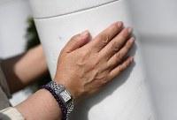 慈しむように「&(安堵)」に触れる女性=千葉県船橋市で2018年5月25日、久保玲撮影