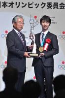 「平成29年度JOCスポーツ賞 表彰式」で特別栄誉賞を受賞し、JOCの竹田恒和会長(左)からトロフィーを受け取り写真撮影に応じる羽生結弦=東京都千代田区で2018年6月8日、西本勝撮影
