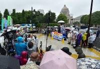雨の中、国会前で安倍政権の退陣などを要求する人たち=東京都千代田区で2018年6月10日午後3時39分、竹内紀臣撮影