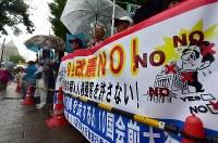 雨の中、国会(左奥)前で安倍政権の退陣などを要求する人たち=東京都千代田区で2018年6月10日午後3時23分、竹内紀臣撮影