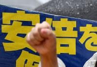 雨の中、国会前で安倍政権の退陣などを要求し、突き上げられた拳=東京都千代田区で2018年6月10日午後3時49分、竹内紀臣撮影