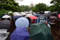 雨の中、国会周辺で安倍政権の退陣などを要求し、声を上げる人たち=東京都千代田区で2018年6月10日午後2時56分、竹内紀臣撮影