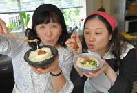「明太とろろご飯」と「梅とろ茶漬け」を持ち、笑顔の西原理恵子さん(右)、枝元なほみさん=手塚耕一郎撮影