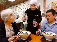 川上勲さん(中央)は障害によって対人関係を築くのが難しかったが、ここで働いてから表情が明るくなったという。母あけみさん(左)は「頑張ってるね」と声を掛けた=大阪市住吉区で、山田尚弘撮影