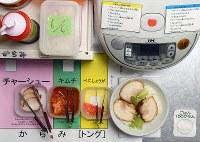 炊飯ジャーの周りには、丼の作り方がわかりやすく示されていた=大阪市住吉区で、山田尚弘撮影