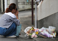A woman prays in front of a spontaneous memorial to Yua Funato, who died of suspected neglect in March this year, in front of the apartment where she lived with her parents, on June 8, 2018, in Tokyo's Meguro Ward. (Mainichi)